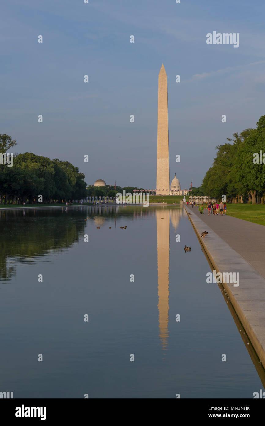 Visitors stroll on summer evening, Washington Monument on the Reflecting Pool, Washington DC, USA, North America - Stock Image