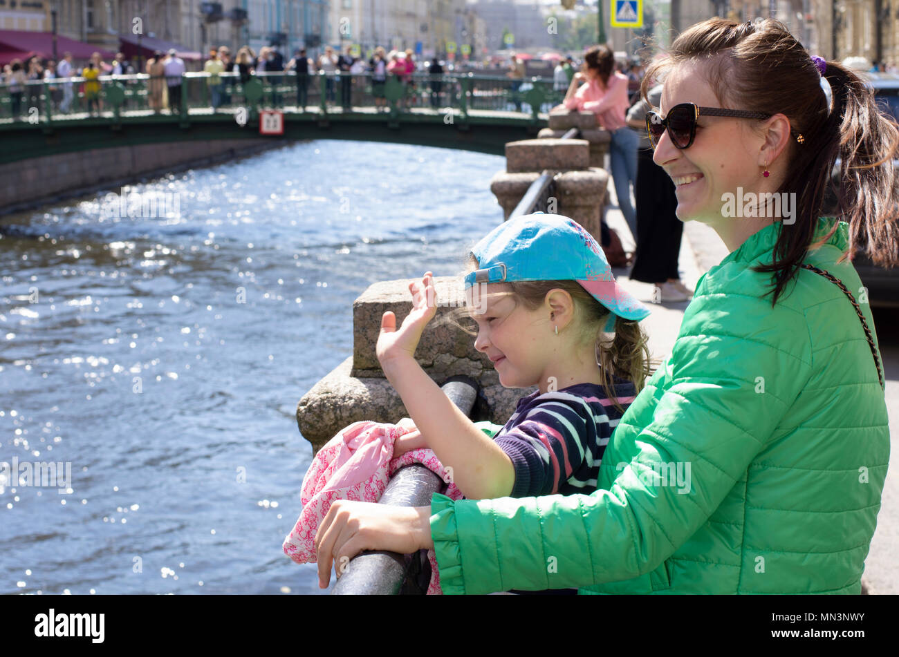 Young mother with the daughter smile and welcome tourists in sunny summer and windy day. On a blurred background Griboyedov canal in St. Petersburg - Stock Image