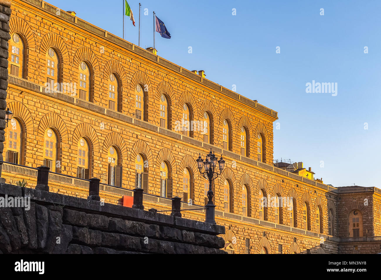 Golden sunlight hit the facade of Palazzo Pitti (Pitti Palace) in Florence, Italy at sunset - Stock Image