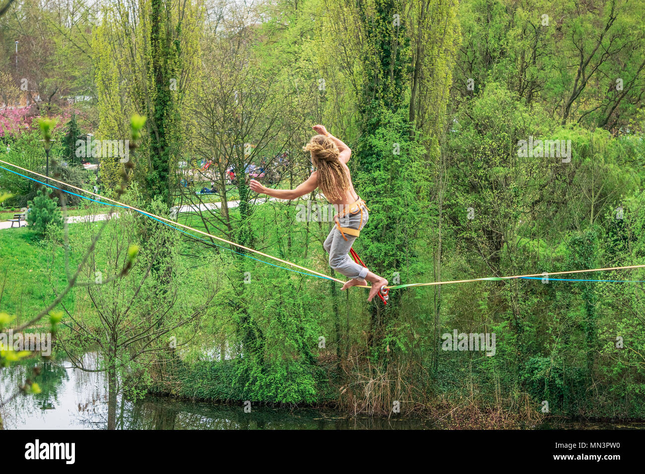 Young male tightrope walker walking on a slackline suspended in the air in a park, Strasbourg, France. - Stock Image