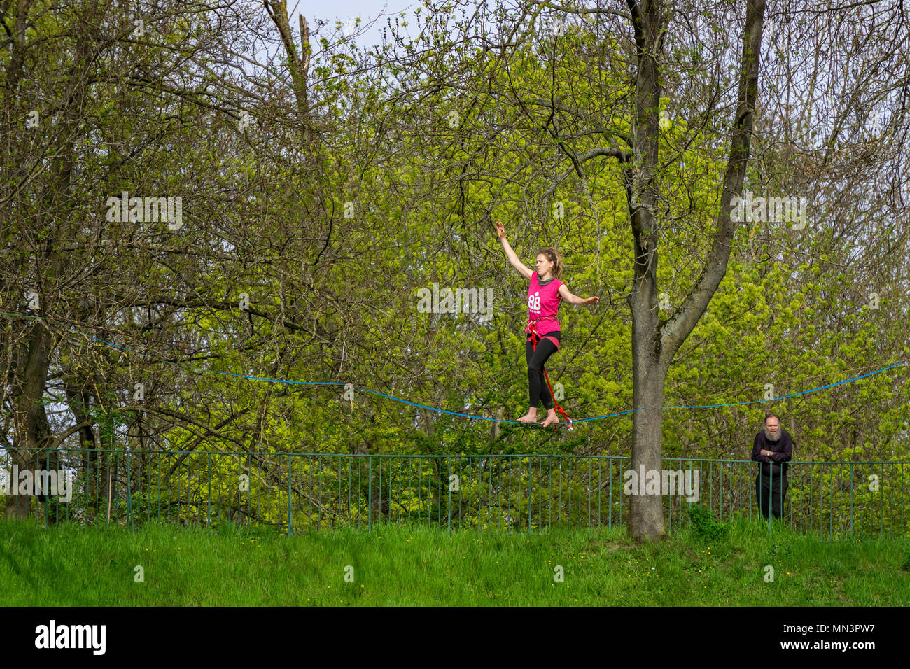Young female tightrope walker walking on a slackline suspended in the air in a park, Strasbourg, France. - Stock Image