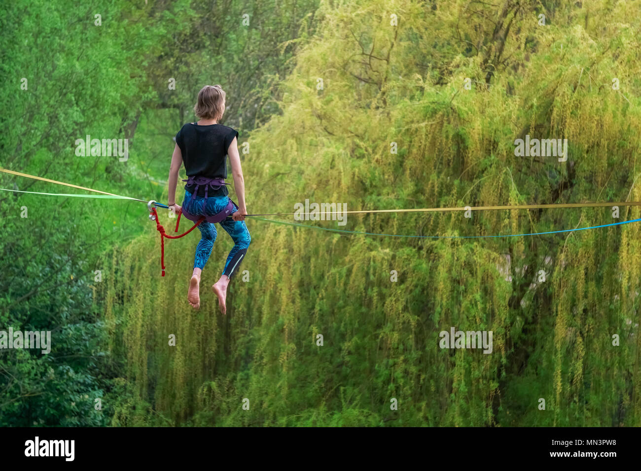 Back view of a young female tightrope walker sitting on a slackline in heights looking ahead in a park. - Stock Image