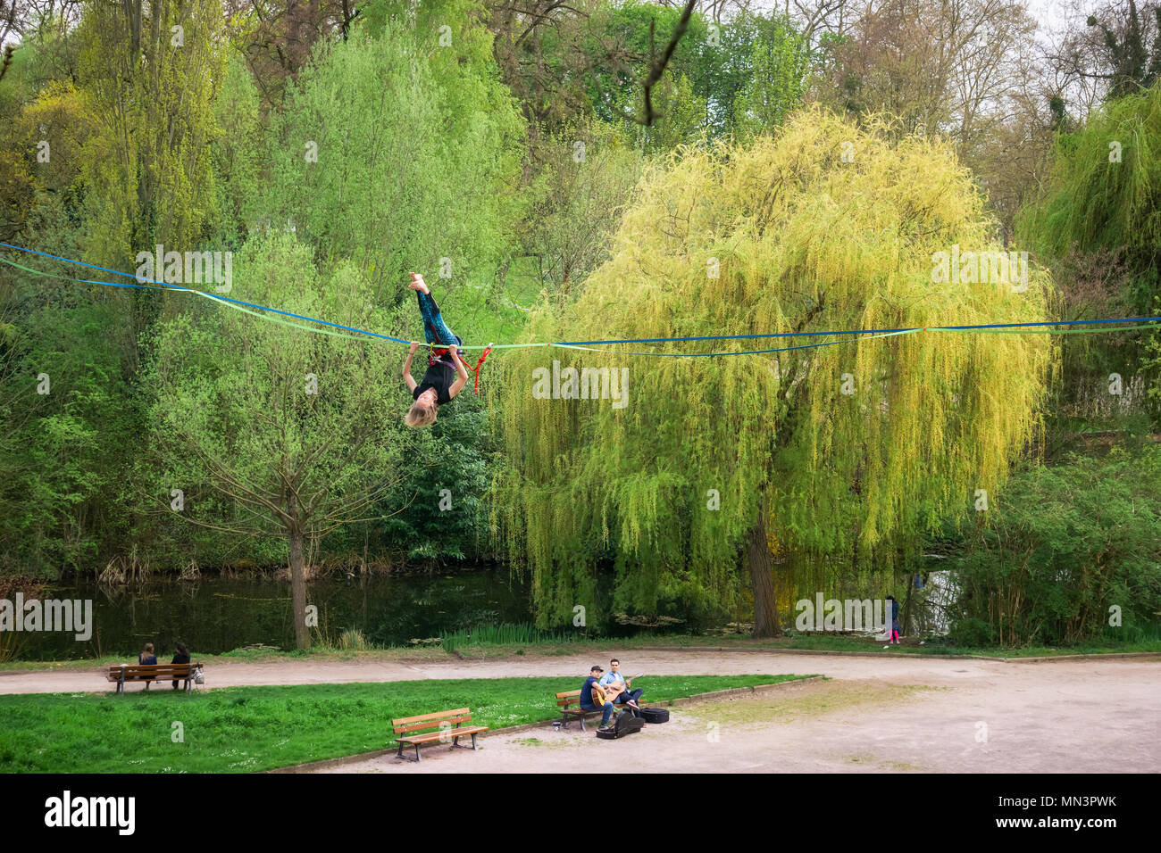 Young woman tightrope walker performing acrobatic tricks on a slackline in heights in a park, Strasbourg, France. - Stock Image