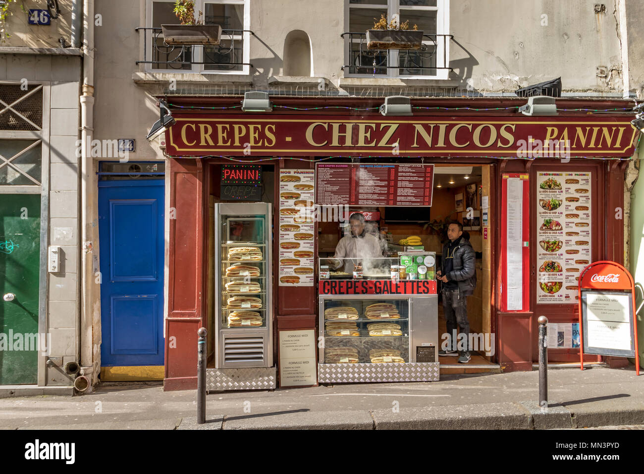 Man buying crepes at Chez Nico's Creperie ,Rue Mouffetard, Paris, France - Stock Image