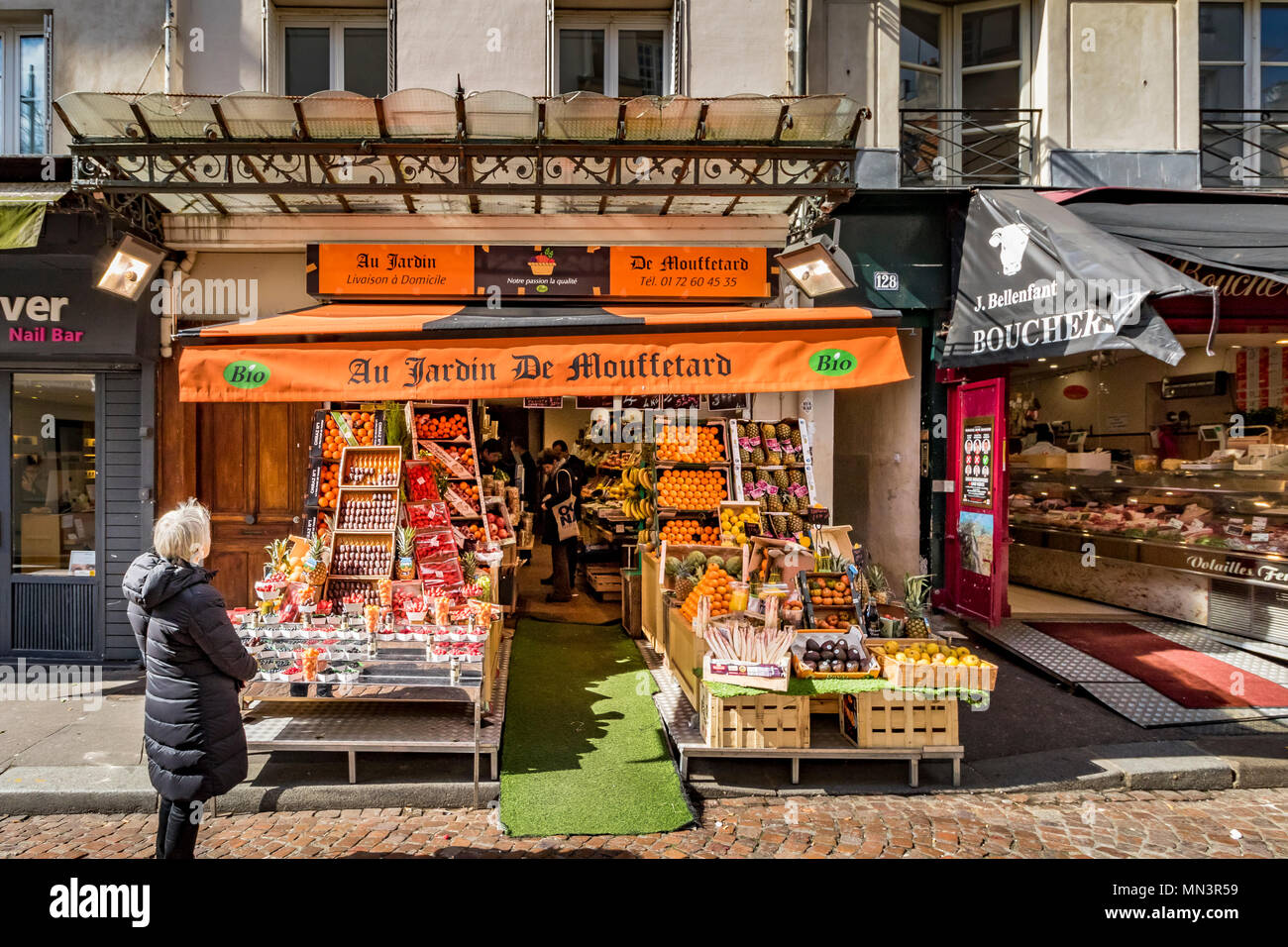 A woman looking at  Au Jardin De Mouffetard ,a fruit and vegetable shop on Rue Mouffetard, Paris, France - Stock Image