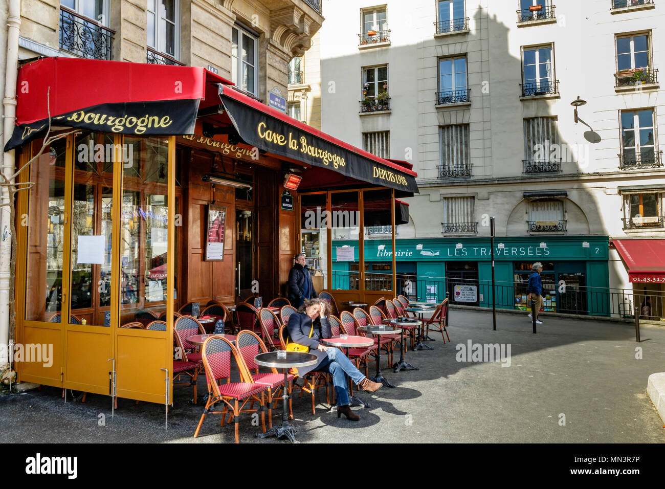 A woman relaxing in a chair enjoying the winter sunshine at Cave La Bourgogne a restaurant on Rue Mouffetard ,Paris ,France - Stock Image