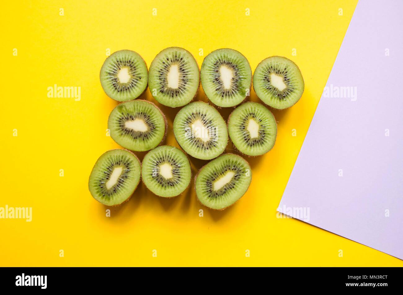 Many halves of kiwi fruit on bright yellow background. - Stock Image