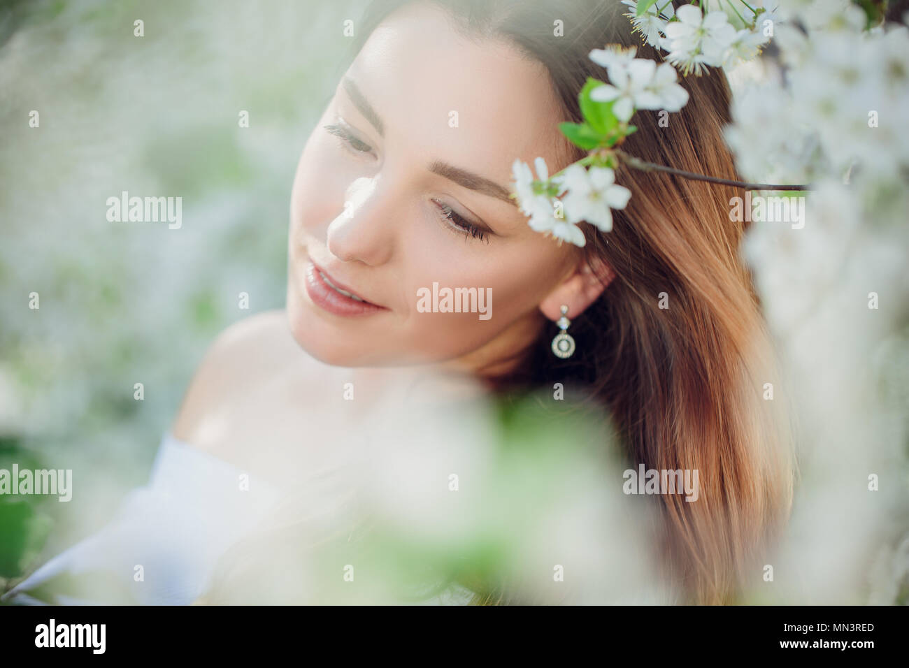 Young beautiful blonde woman in blooming almonds garden. White flowers at spring. blurring - Stock Image