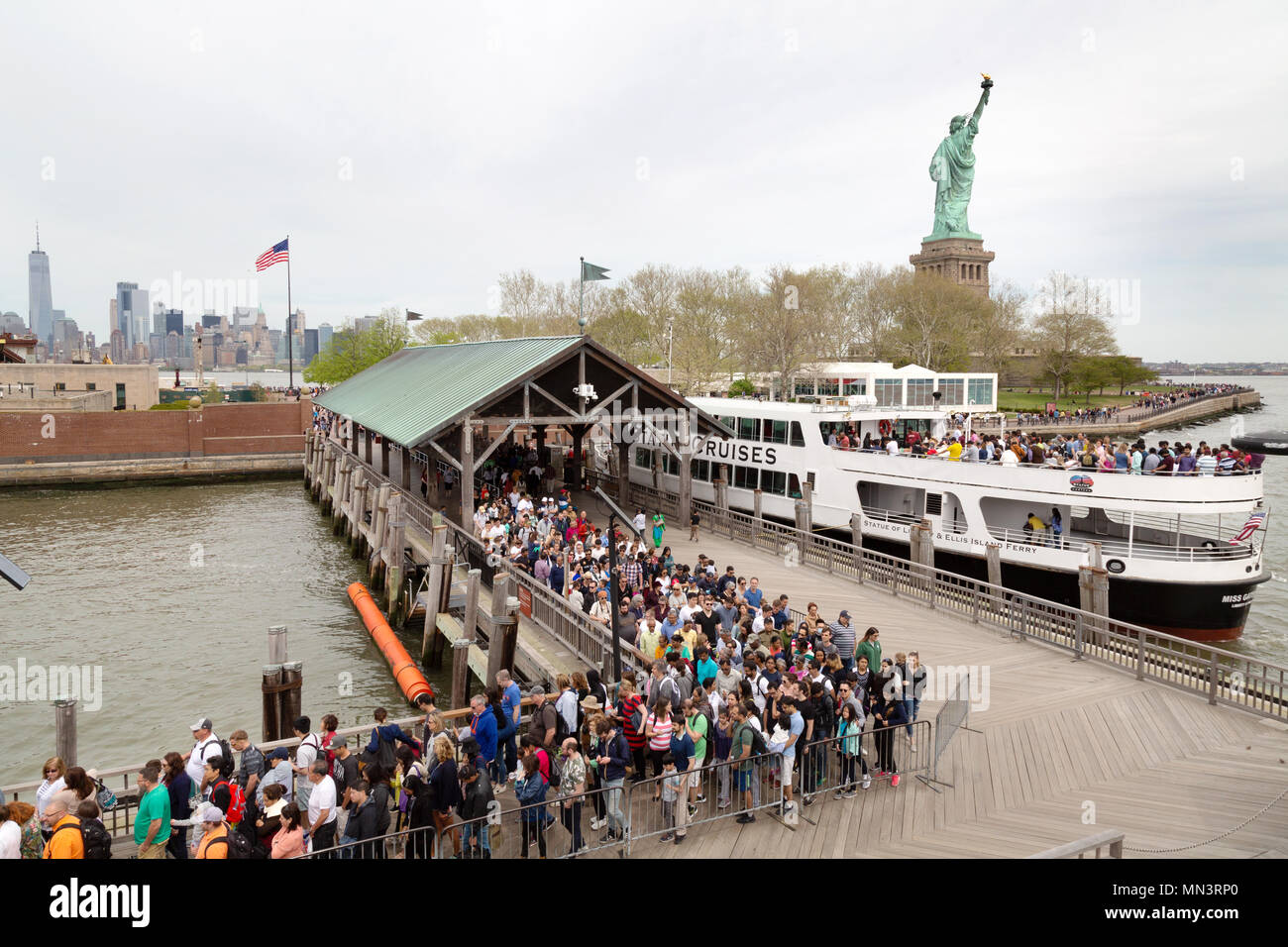 Tourists boarding a cruise boat at the dock on Liberty Island, with the Statue of Liberty, Liberty Island, New York city, USA Stock Photo