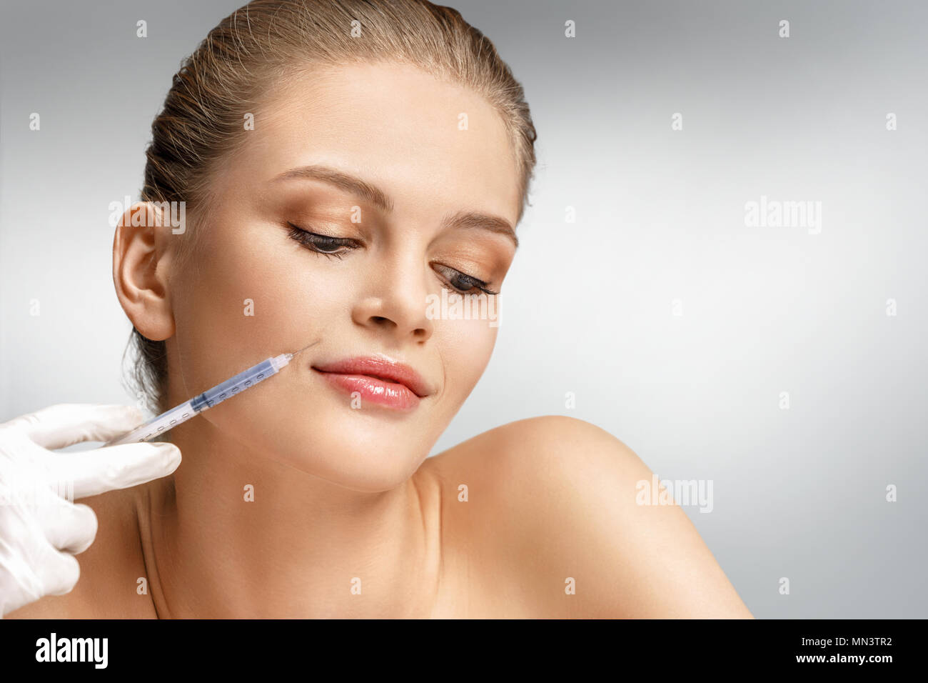 Beautiful woman face and beautician hands with syringe making rejuvenate injection. Clean Beauty concept Stock Photo