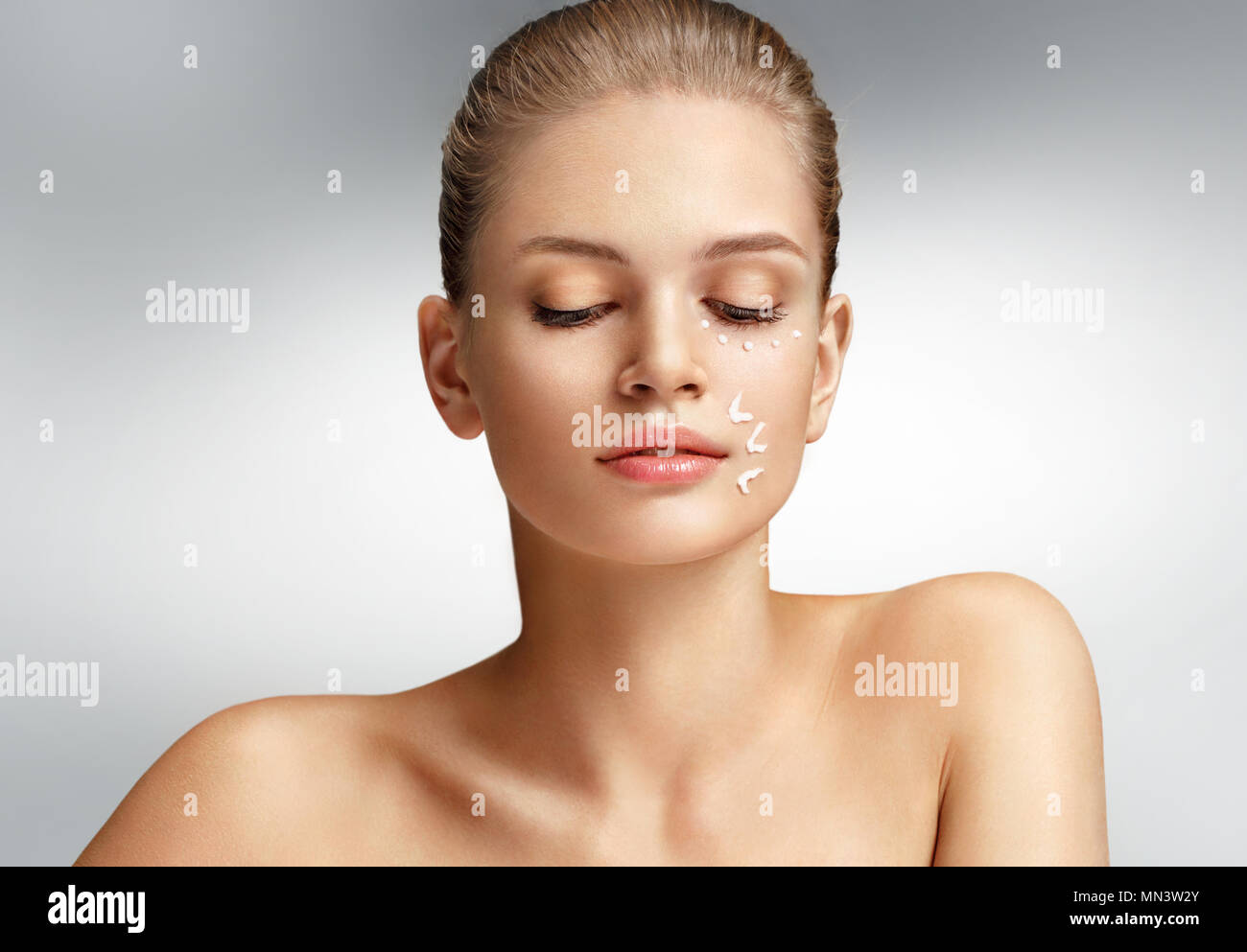 Attractive woman with perfect skin on grey background. Skin care concept Stock Photo