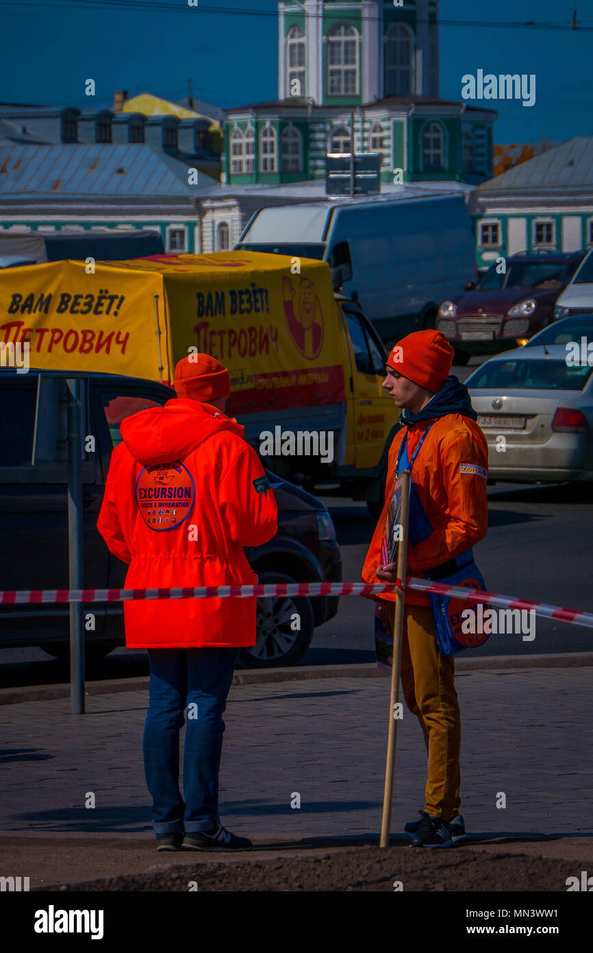 ST. PETERSBURG, RUSSIA, 01 MAY 2018: Outdoor view of unidentified teenagers wearing a orange jacket written the words official city guide, holding information in their hands in st. Peterburg - Stock Image