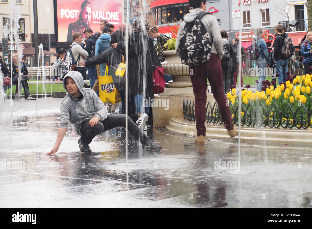 Young teenagers playing in the fountains in Leicester Square, London with other pedestrians around - Stock Image