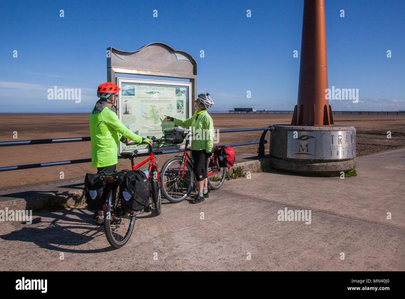 Southport, Merseyside. UK Weather. 14/05/2018. Bright sunny start to the day as Mark & Jenny check their route before setting off on a coast to coast cycle ride. The Trans Pennine Trail (TPT) is a route for walkers and cyclists. The Trail from coast-to-coast between Southport and Hornsea is 215 miles.  The Trans Pennine Trail is mapped and signed all the way, mainly traffic free and is surprisingly level considering the dramatic scenery along the way. Credit: MediaWorldImages/AlamyLiveNews. - Stock Image