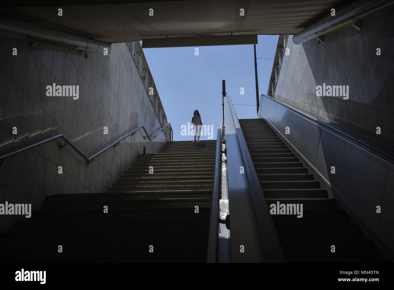 Athens, Greece. 14th May, 2018. A woman looks down at a closed metro station during a 24-hour strike called by metro workers to protest shortages in both staff and equipment in Athens, Greece, May 14, 2018. Credit: Marios Lolos/Xinhua/Alamy Live News - Stock Image
