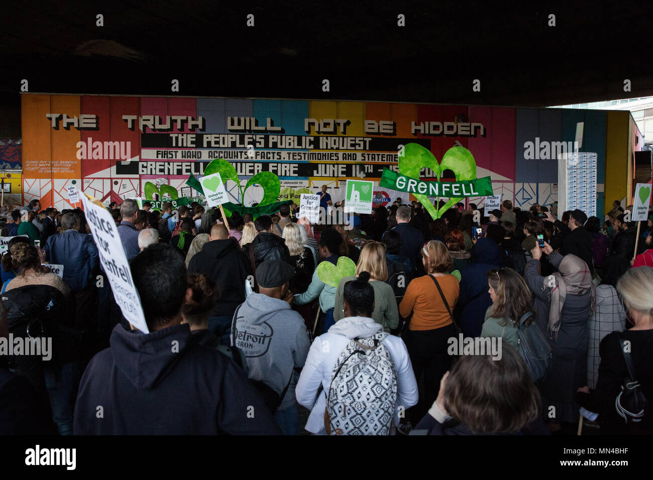 London, UK. 14th May, 2018. Members of the Grenfell community listen to speeches under the Westway flyover at Latimer Road at the end of the Grenfell Silent March. The march, which takes place on the monthly anniversary of the fire on 14th June 2017, has now returned to the original route starting at the Notting Hill Methodist Church. 71 people died in the Grenfell Tower fire and over 70 were injured. Credit: Mark Kerrison/Alamy Live News Stock Photo