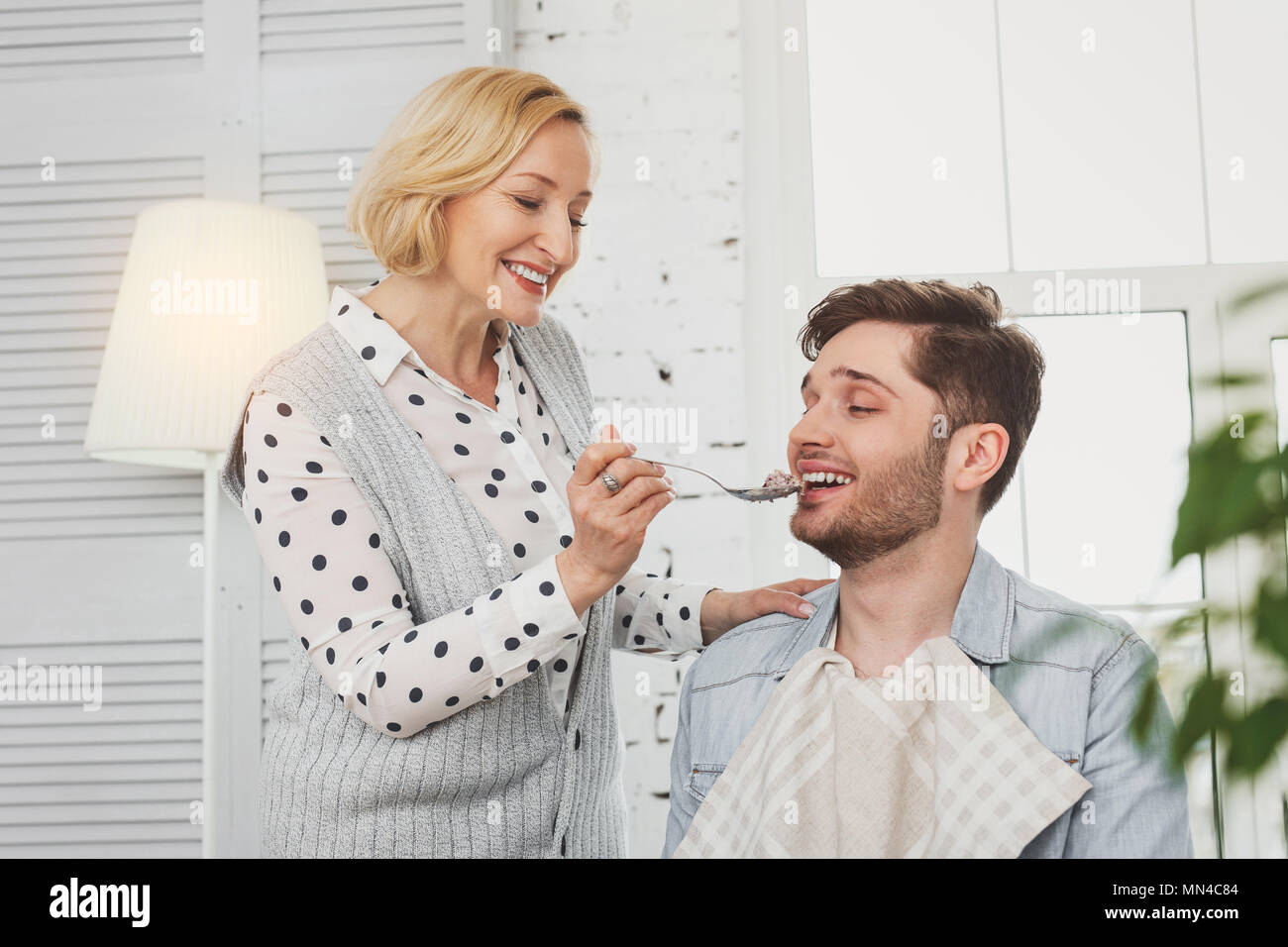Positive aged woman feeding her son - Stock Image