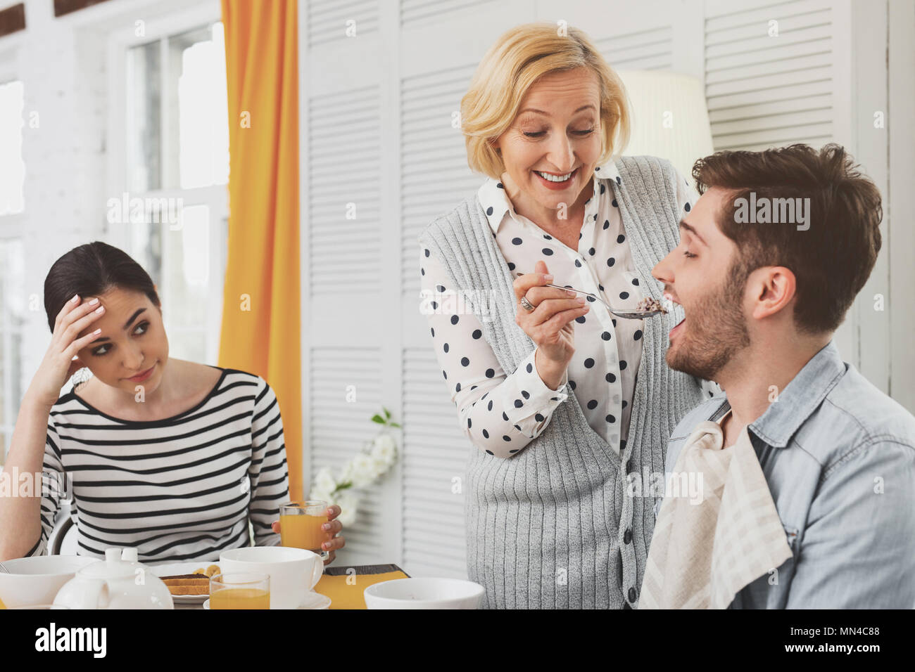 Happy aged woman holding a spoon - Stock Image