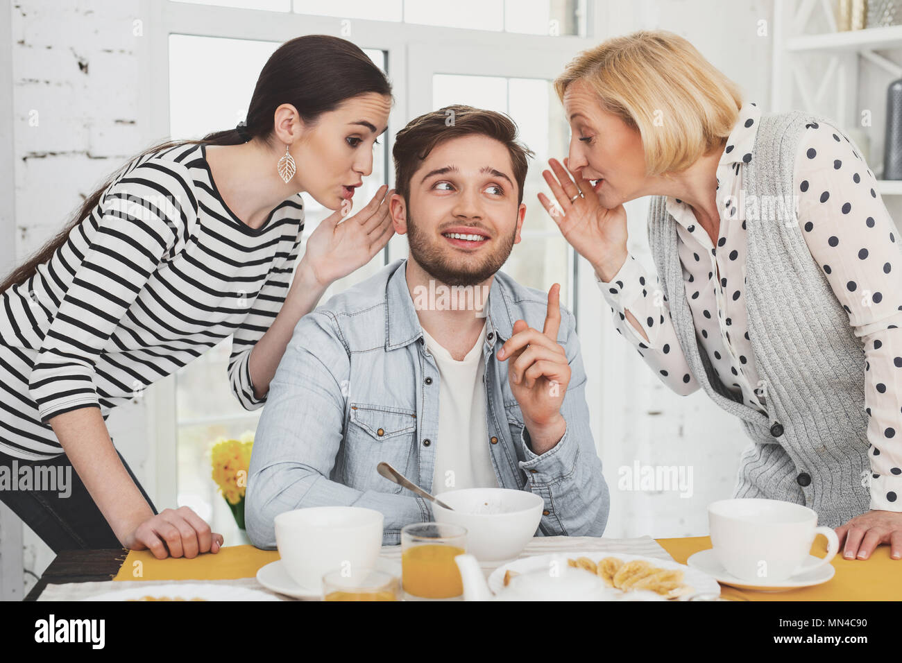 Joyful nice man being in between his wife and mother - Stock Image