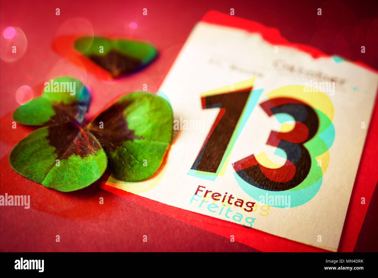 Calendar Sheet Friday the 13th and shredded clover, Kalenderblatt Freitag der 13. und zerrissenes Kleeblatt - Stock Image