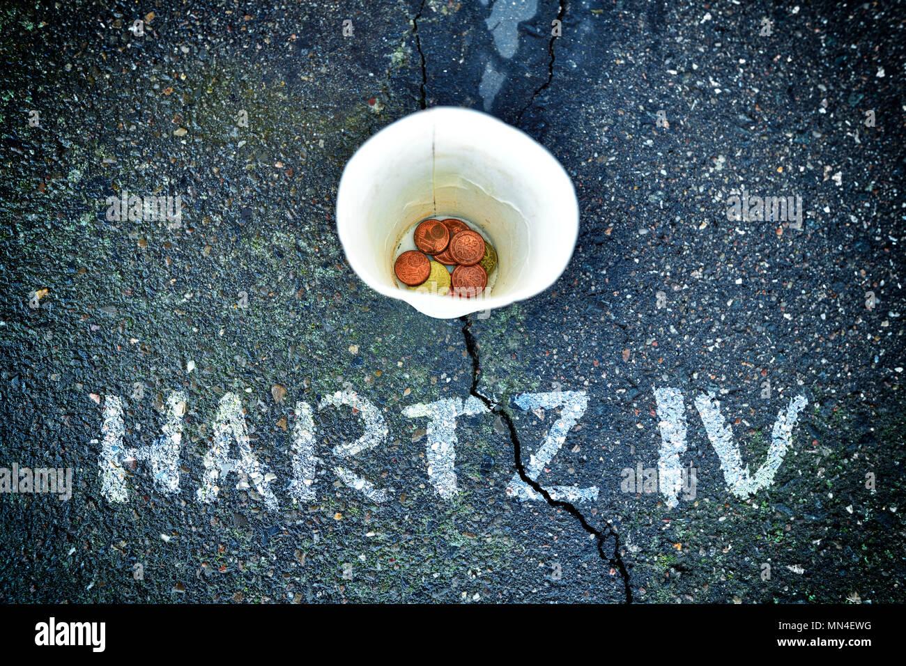 Donate money and cup with small lettering Hartz IV, Spendenbecher mit Kleingeld und Schriftzug Hartz IV - Stock Image