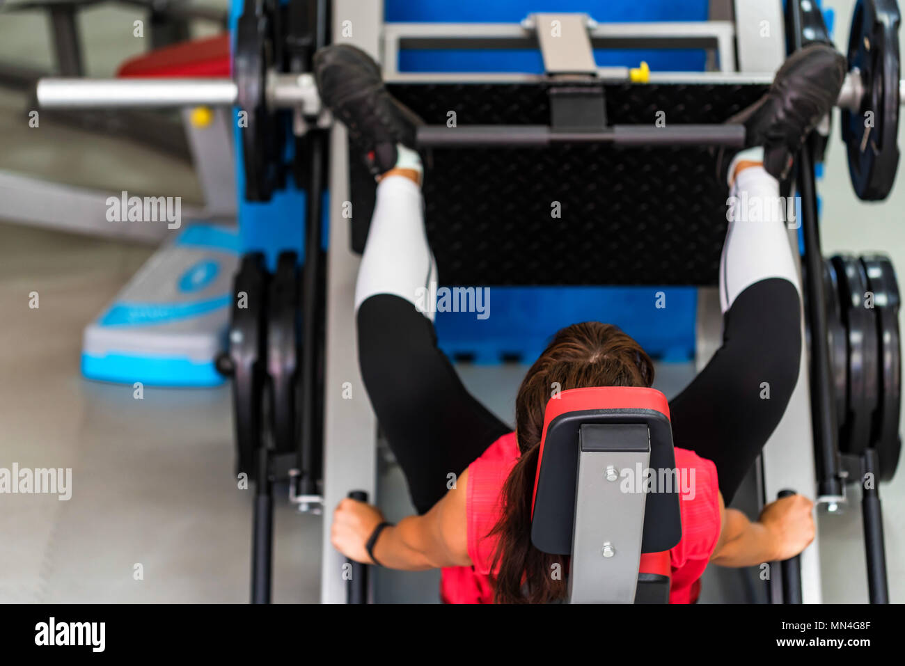Young sporty woman does leg exercises in gym - Stock Image