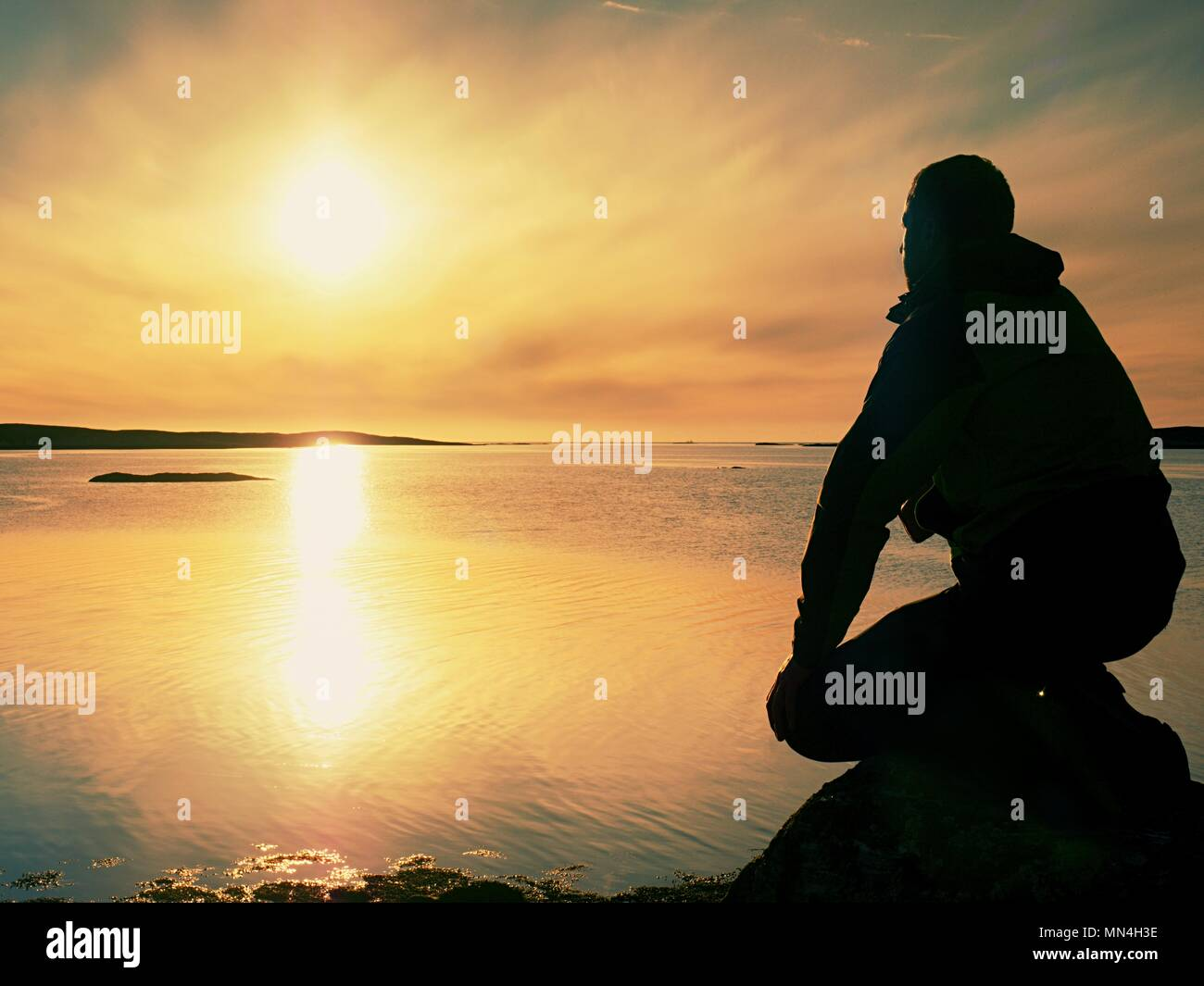 Lonely man hiker sits alone on the rocky  coast and  enjoying sunset. View over rocky cliff to free ocean - Stock Image