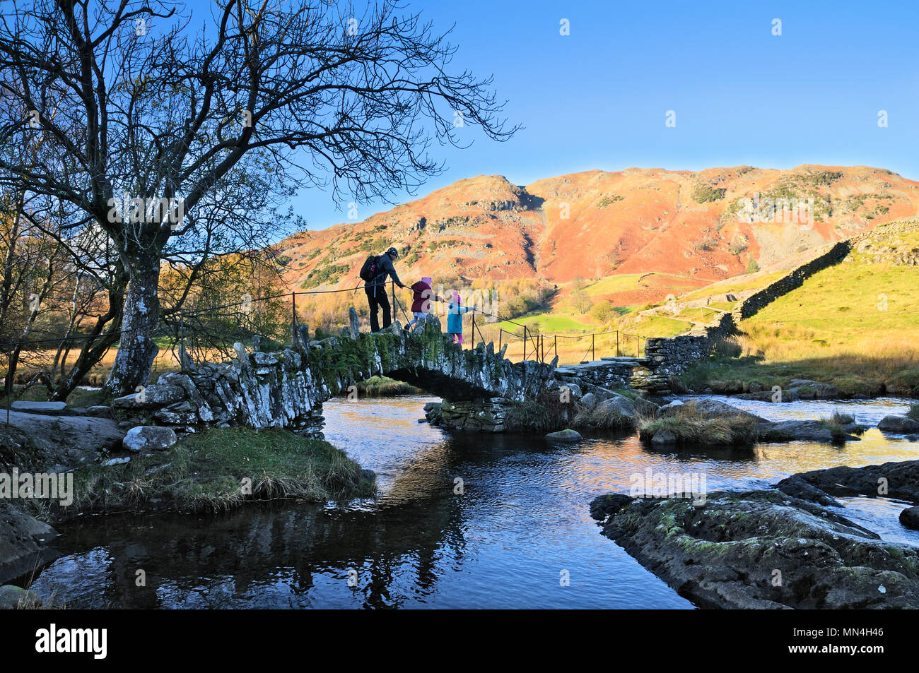 Father and children walking over Slater Bridge across the River Brathay against a backdrop of Lingmoor Fell, Little Langdale, Lake District, UK - Stock Image