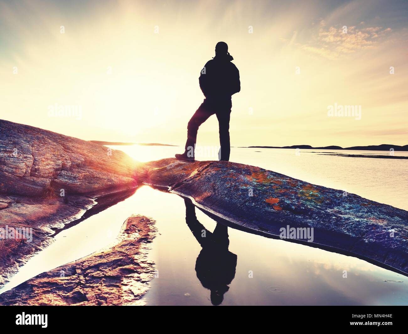 Silhouette of man in outdoor clothes on rocky cliff above sea. Hikerthinking  during sunset in the background. Traveling away concept. - Stock Image