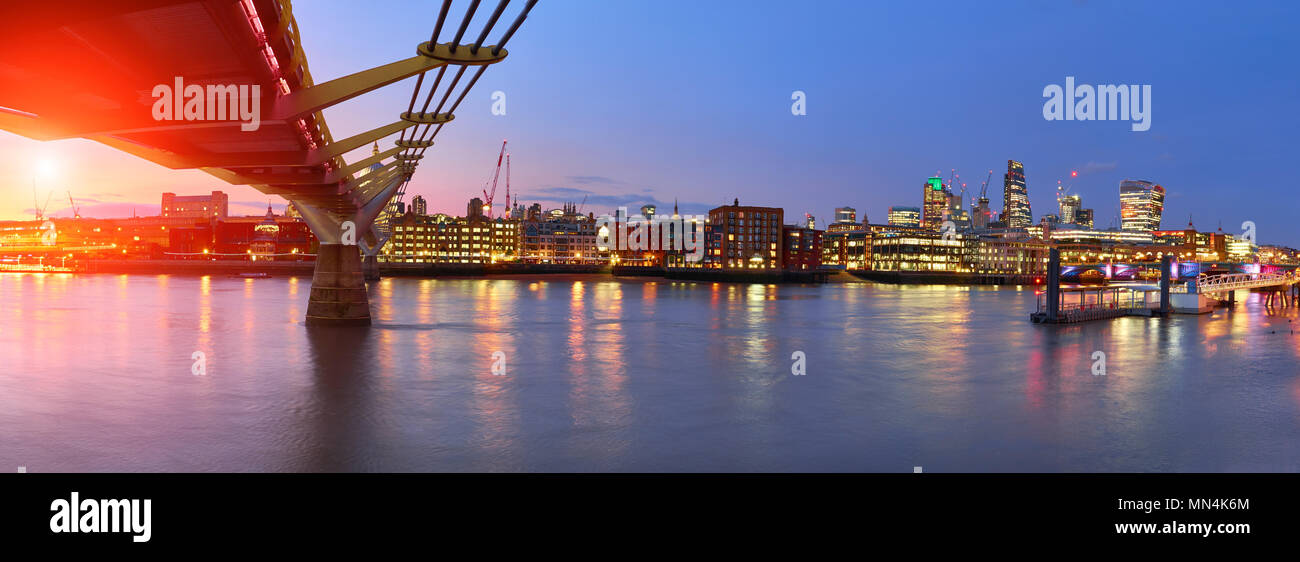 London at sunset, Millennium bridge leading towards illuminated St. Paul cathedral over Thames river with city bathing in electric light. Panoramic to - Stock Image