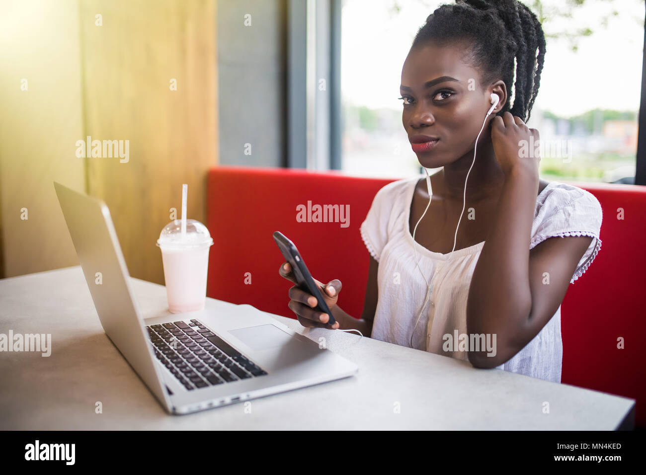 Cheerful female black model resting in coffee shop listening favorite music in headphones and chatting in networks.Beautiful dark skinned freelancer e - Stock Image