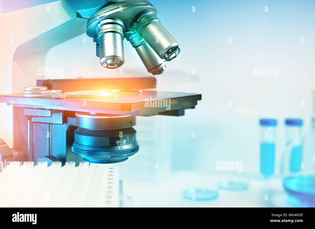 Scientific background with closeup on light microscope and laboratory out of focus. This image is toned. Shallow DOF, focus on the slide glass. - Stock Image