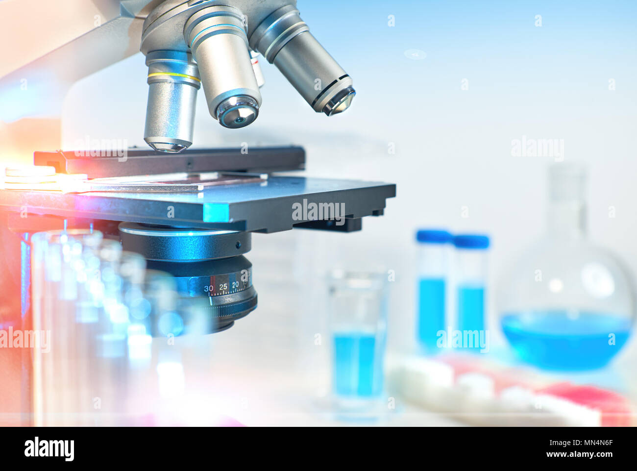 Scientific background with closeup on light microscope and laboratory out of focus. This image is toned. - Stock Image