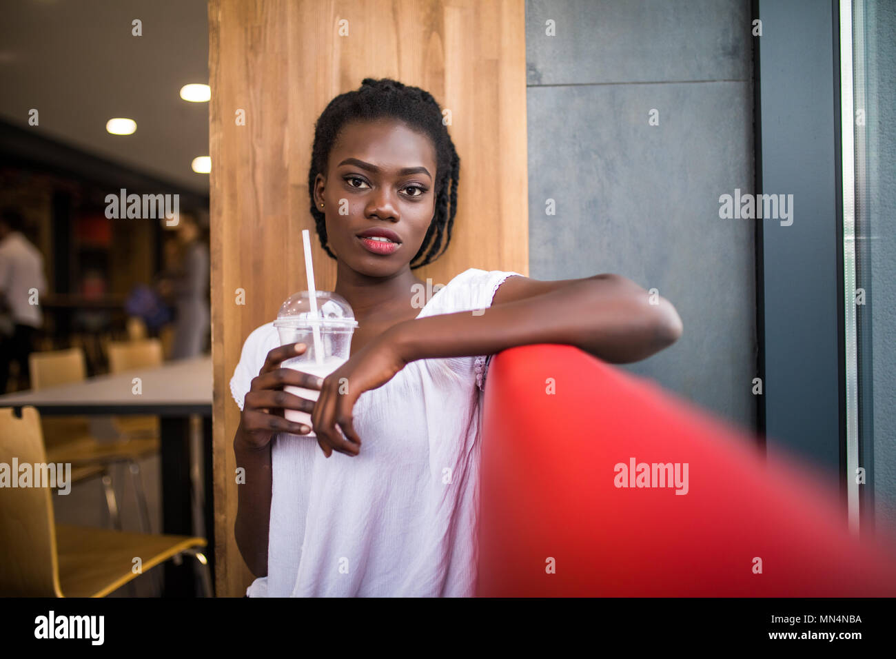 Photo of positive dark skinned afro american female ejoys good rest at coffee shop, drinks beverage. People, leisure and eating concept Stock Photo