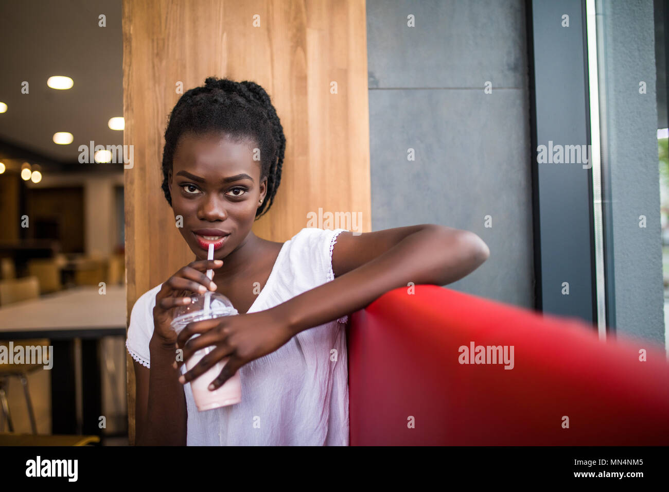 Photo of positive dark skinned afro american female ejoys good rest at coffee shop, drinks beverage. People, leisure and eating concept - Stock Image