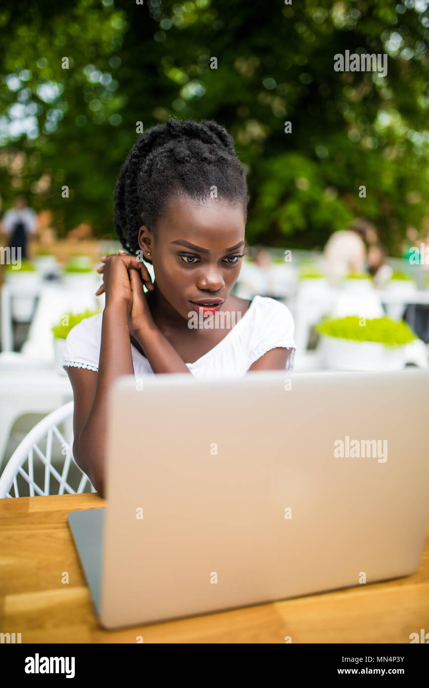 Young afro american black female freelancer working with digital tablet outdoors in street cafe on a sunny day. - Stock Image