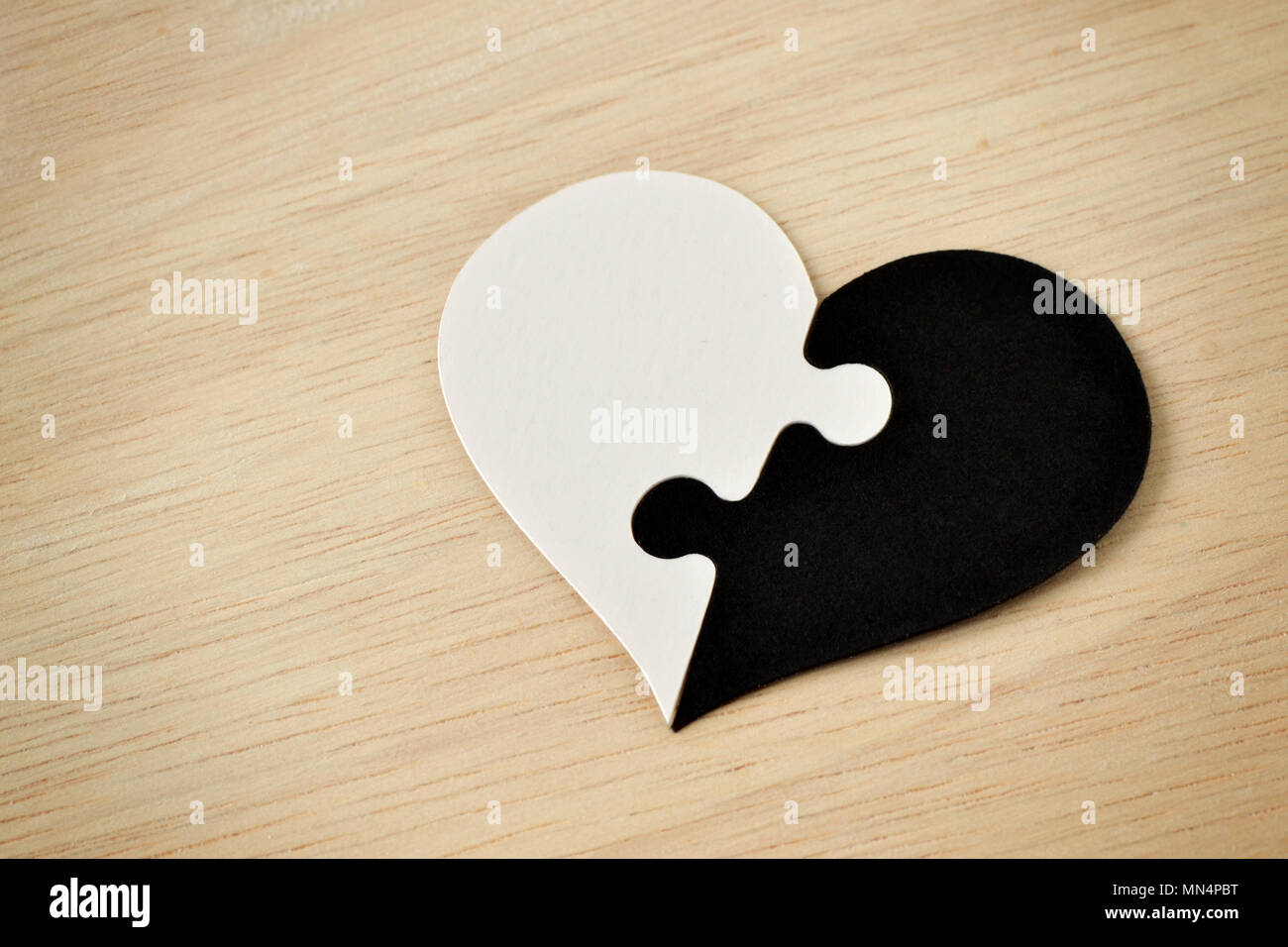 Black and white puzzle heart - Anti-racism concept - Stock Image