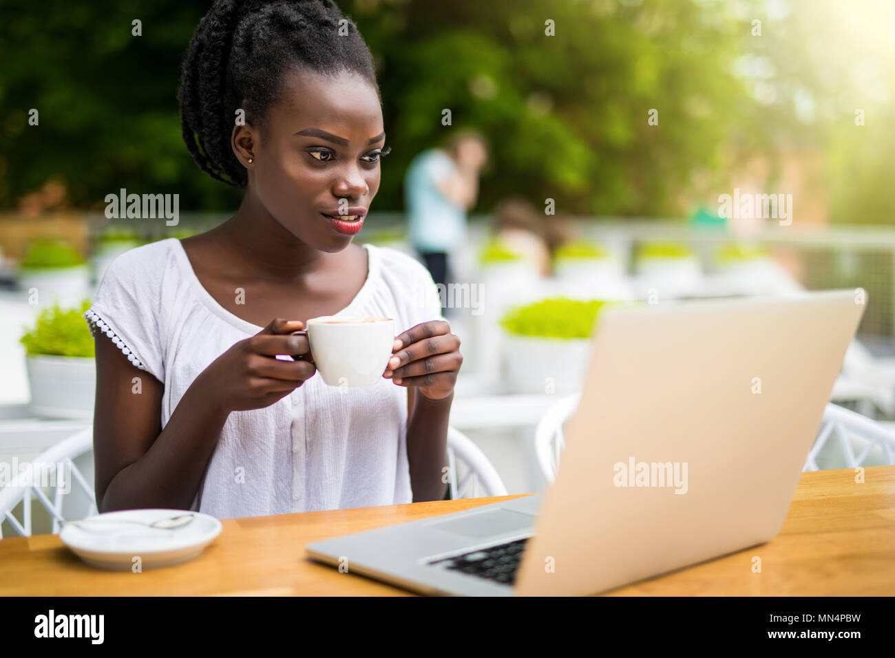 Charming African American woman entrepreneur is sitting at street restaurant and having remote online video session with colleagues using laptop, warm - Stock Image