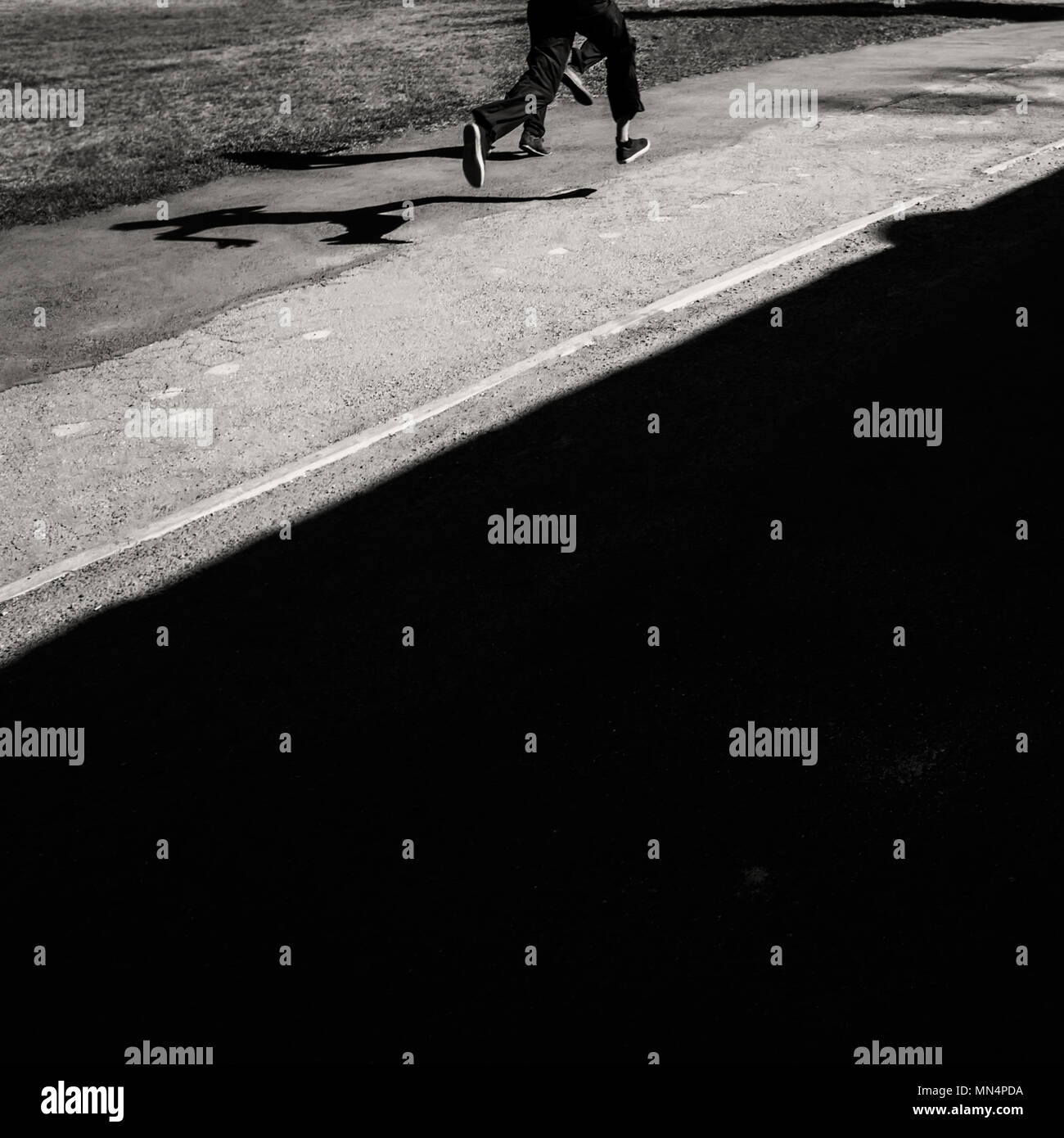 BLURRED DARK BACKGROUND. SHADOWS OF FIGURES AT ASPHALT OF RUNNING BOYS. - Stock Image