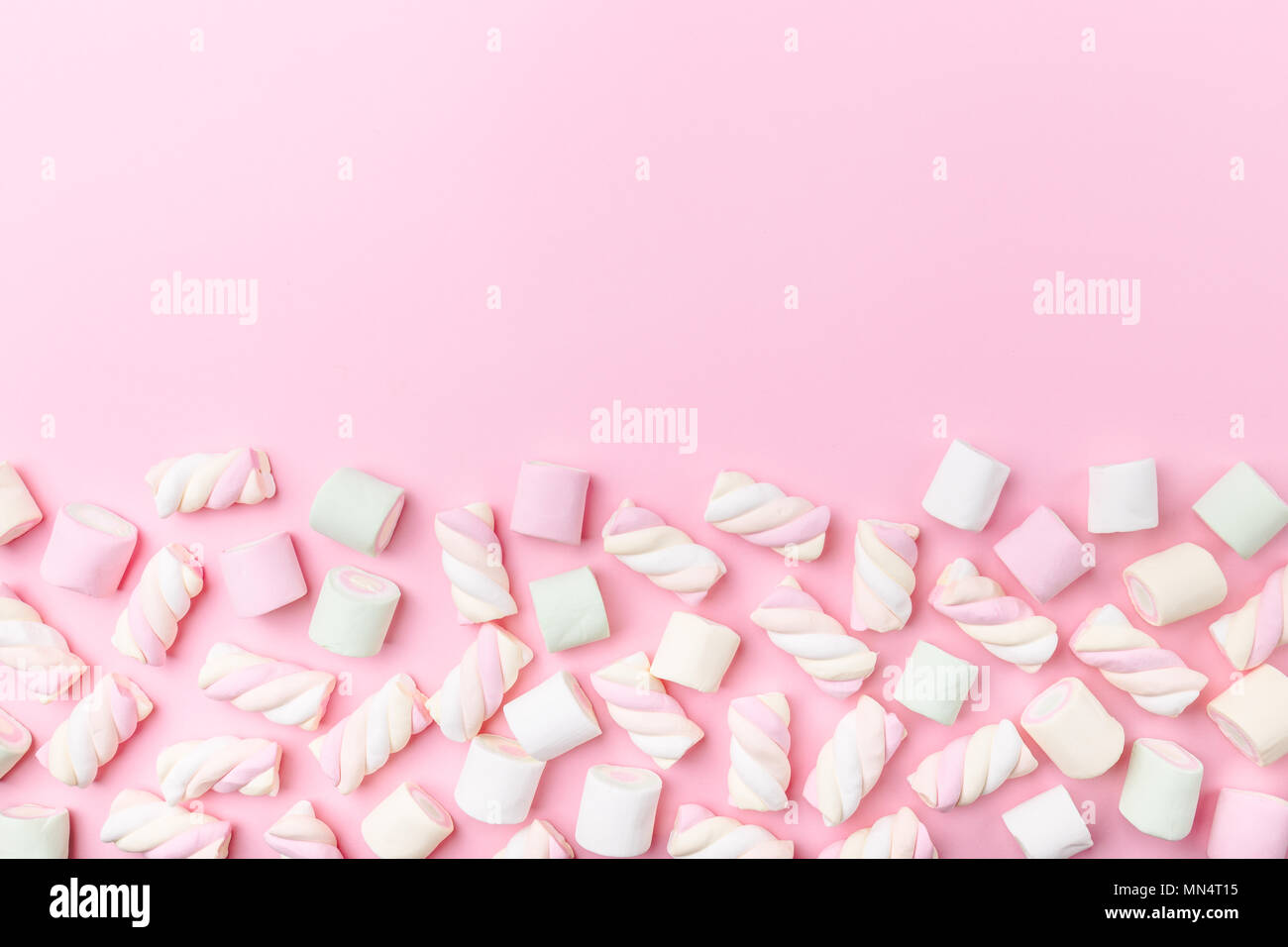 Different pastel color marshmallows on pink pastel background with copy space. Top View. Conceptual Food Trend Flat Lay - Stock Image