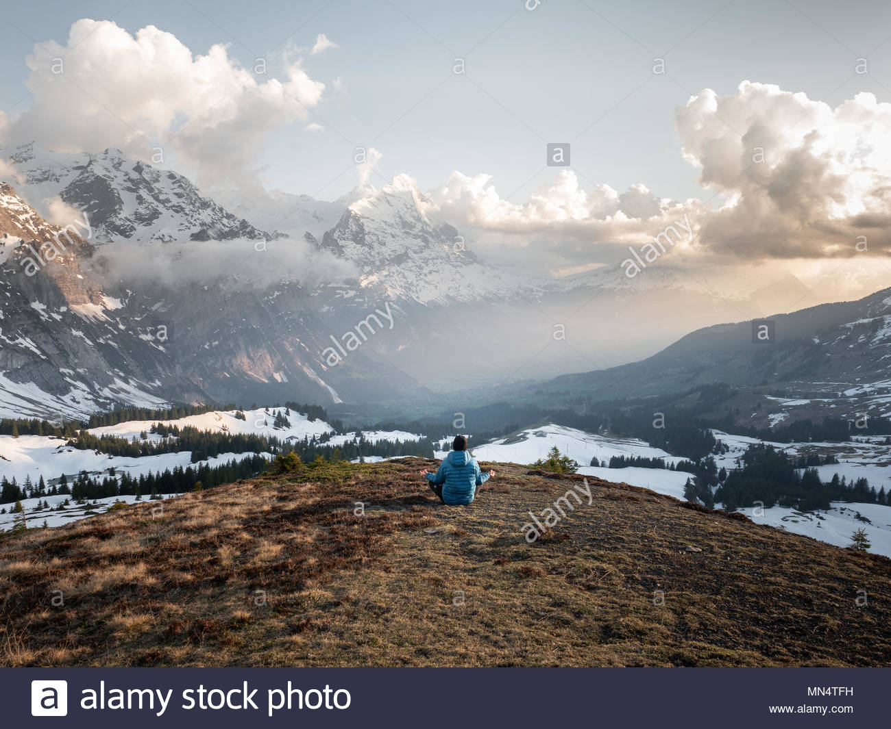single man sitting in front of vast mountain range in the swiss alps meditating, sunrise light and snow covered mountains - Stock Image
