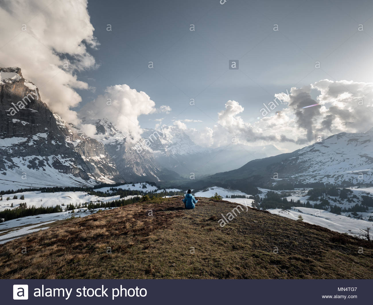 one man meditating in wide open mountain landscape in front of big swiss alps mountain peaks and eiger mountain, for concepts as relaxation, healthy l - Stock Image