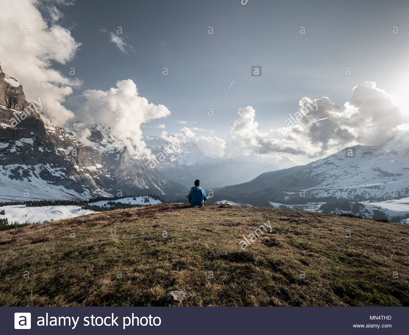 single man sitting on hilltop overlooking the surrounding mountain range and meditating, idyllic alpine scene - Stock Image