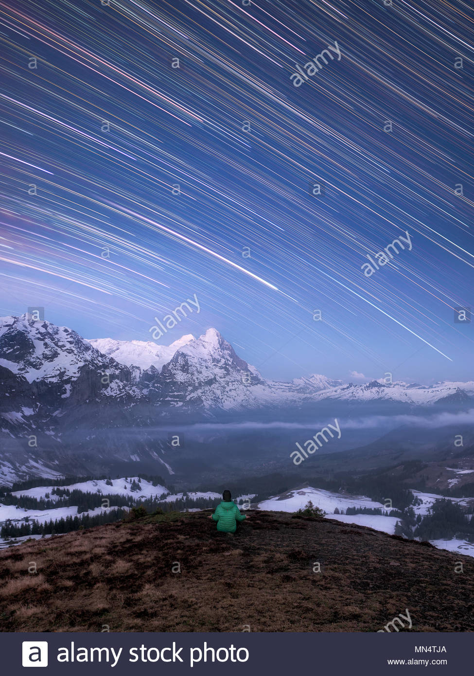 one man sitting under the night sky in the mountains meditating, shooting star like star trails from earth rotation and snow covered alpine landscape, - Stock Image