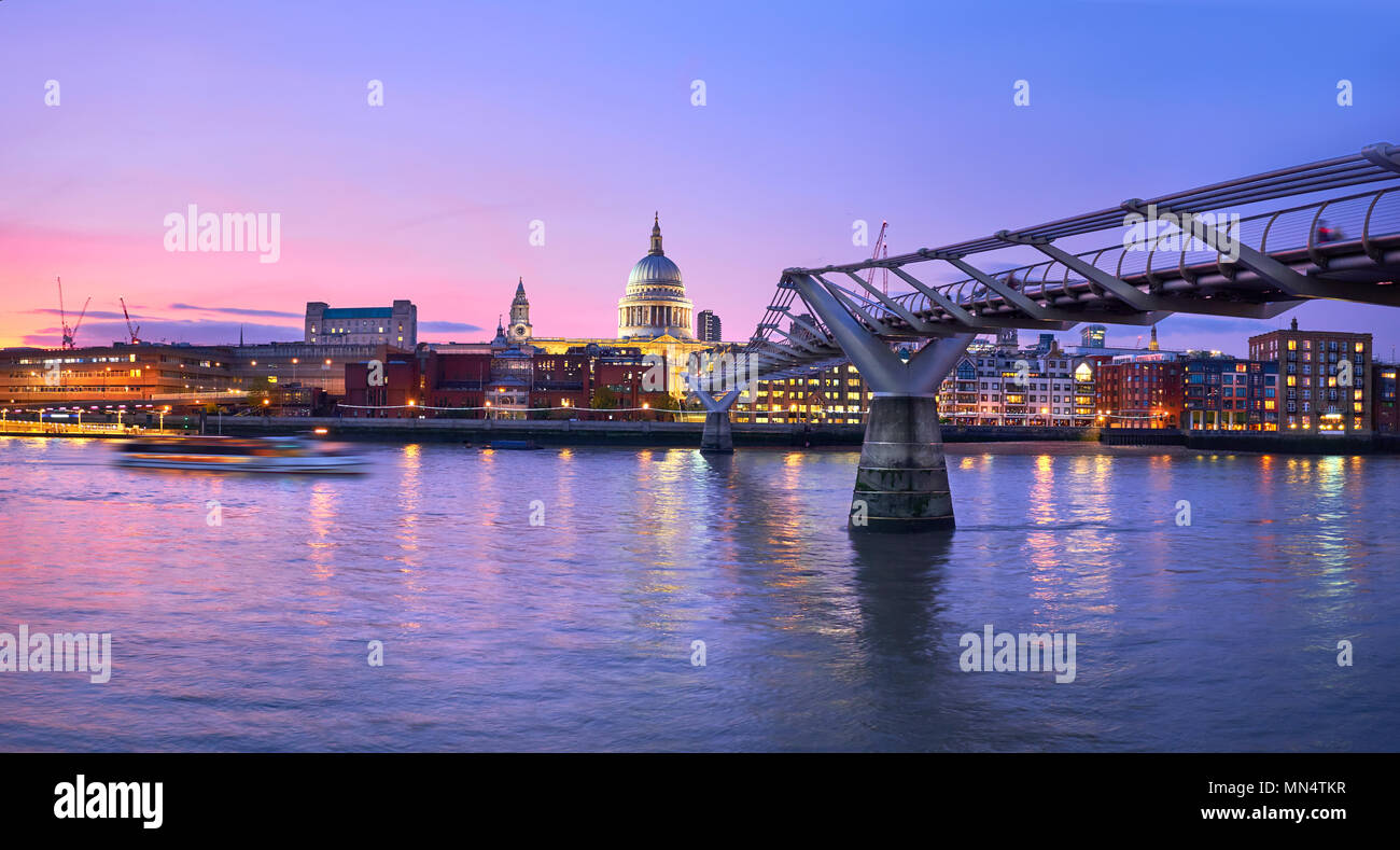 London at sunset, Millennium bridge leading towards illuminated St. Paul cathedral over Thames river with city bathing in electric light. Panoramic to Stock Photo