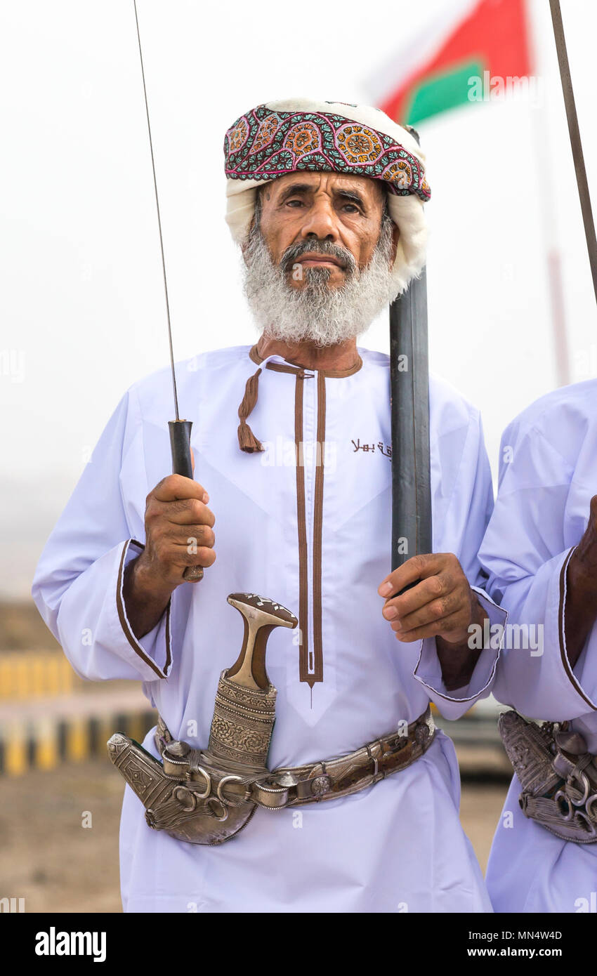 Ibri, Oman, 28th April 2018: omani man with tradiional dagger and a sword, singling tradtitional songs - Stock Image