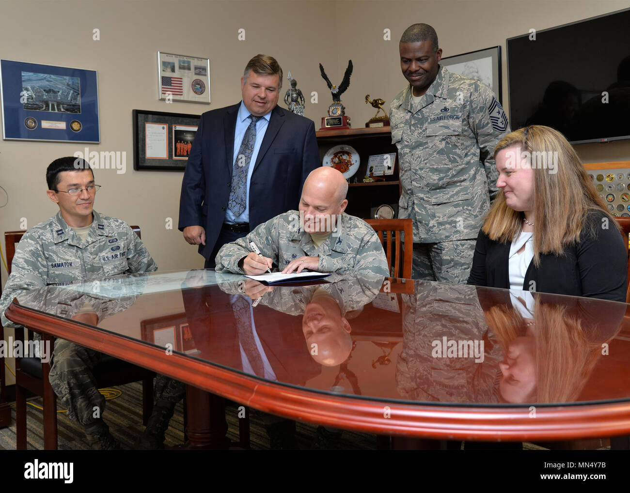 """Col. Roman L. Hund, installation commander, signs a Women's History Month proclamation in his office Aug. 17, while Capt. Abror Samatov and Kerryn Loan, committee members, Tom Fredericks, 66th Air Base Group deputy director, and Command Chief Master Sgt. Henry Hayes look on. The theme for this year's WHM campaign is """"Celebrating Women's Right to Vote."""" (U.S. Air Force photo by Linda LaBonte Britt) Stock Photo"""