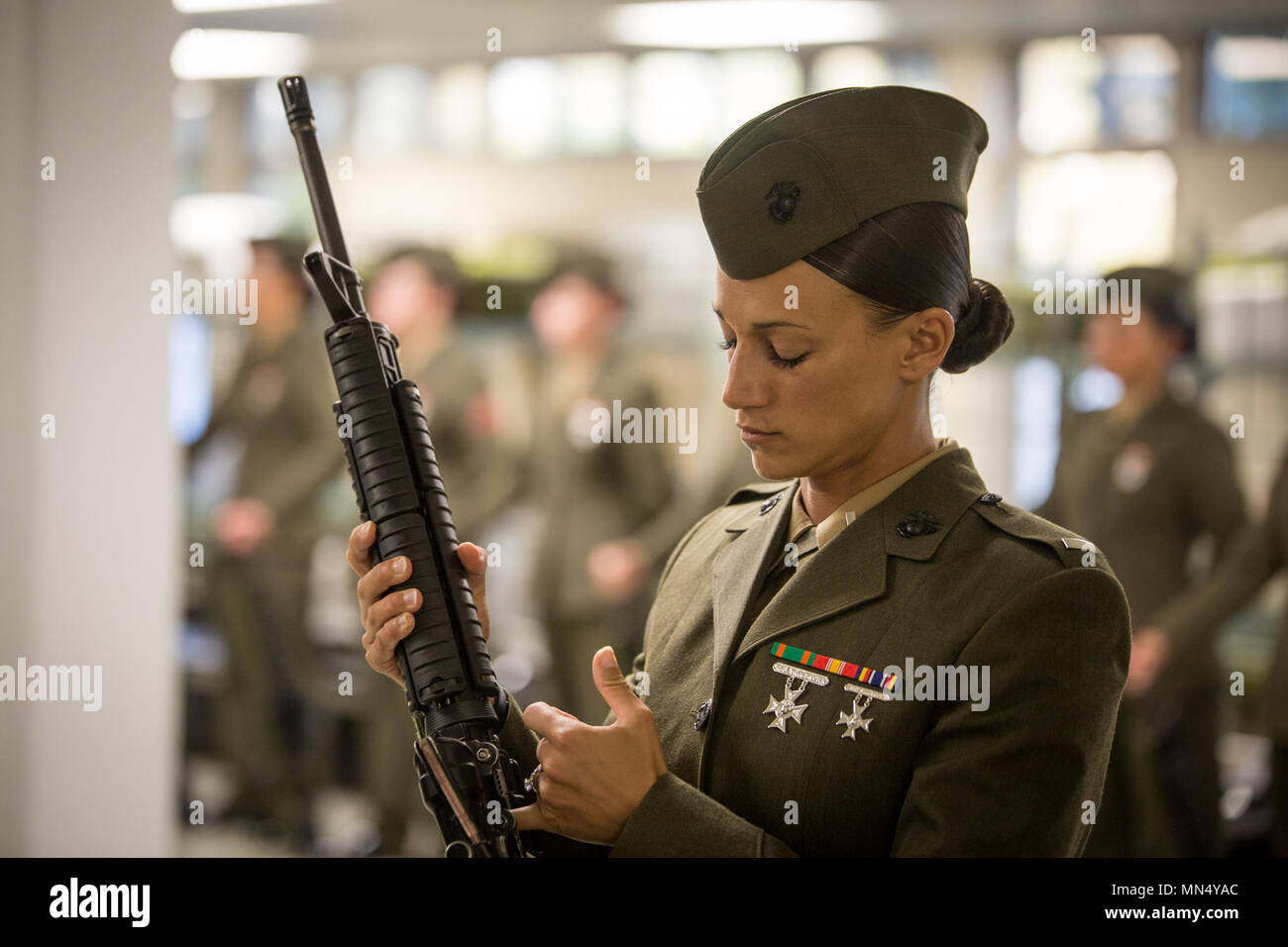 U.S. Marine Corps 1st Lt. Sarah B. Snody, a series commander of November Company, 4th Recruit Training Battalion, inspects a Marine's rifle Aug. 22, 2017, on Parris Island, S.C. Formal inspections held by sergeants and officers, like Snody, 30, from Alton, Ill., ensure Marines have properly fitted uniforms as well as possess attention to detail, bearing, confidence and discipline. Oscar Company is scheduled to graduate Aug. 25, 2017. Parris Island has been the site of Marine Corps recruit training since Nov. 1, 1915. Today, approximately 20,000 recruits come to Parris Island annually for the c - Stock Image