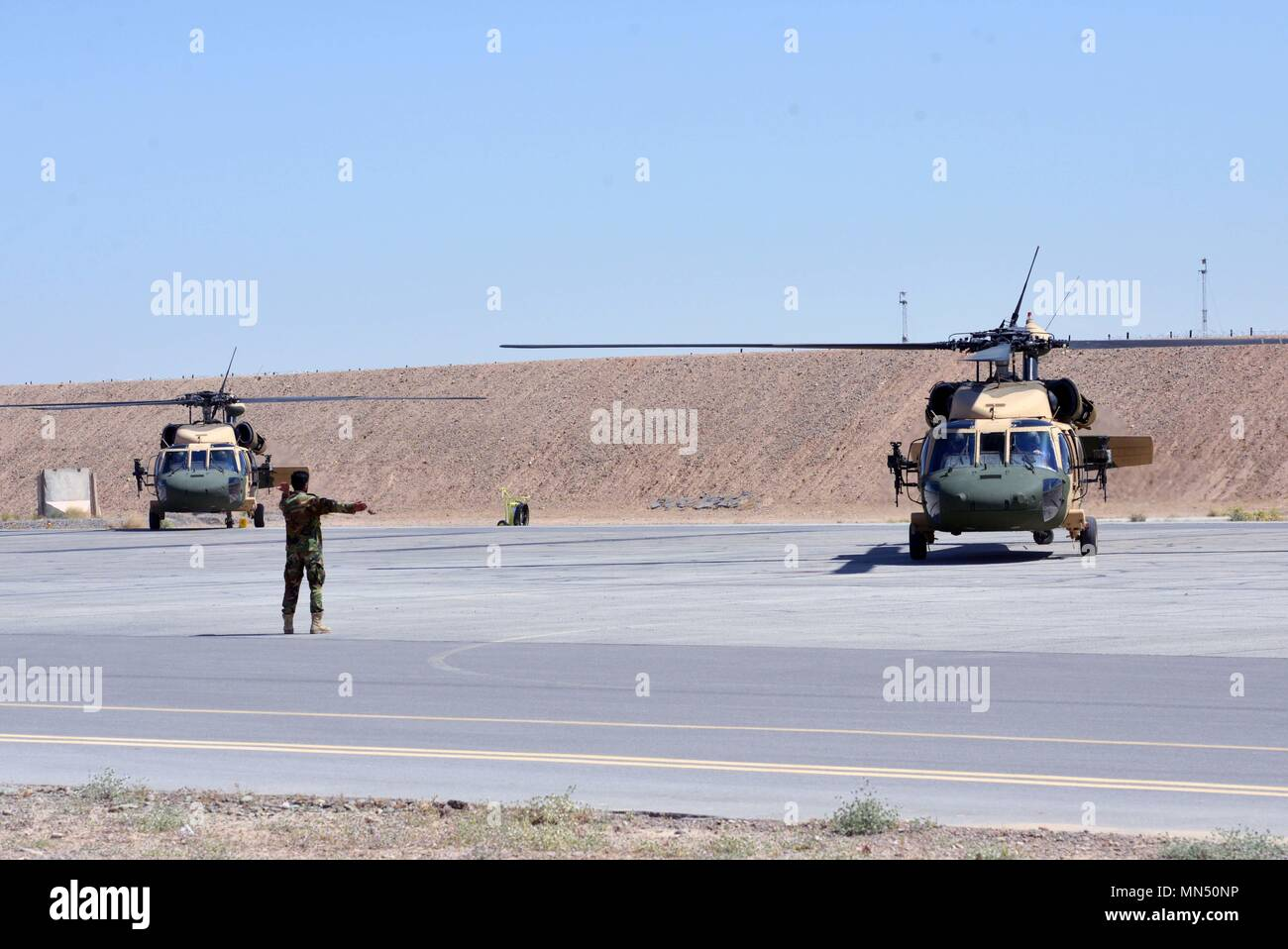 An Afghan Air Force member directs two UH-60 Blackhawks as they prepare to take off for the first Afghan-led operational mission on this aircraft May 8, 2018, Kandahar Air Field, Afghanistan.  The mission, which was in support of the elections, occurred just one day after the crews graduated from Mission Qualification Training. (U.S. Air Force photo/1st Lt. Erin Recanzone) - Stock Image