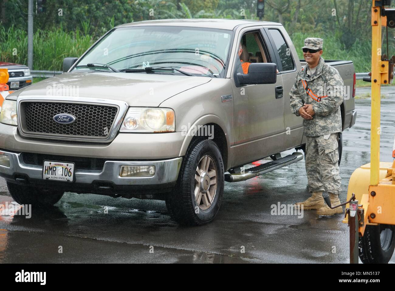 SPC Robert Harrington, Task Force Hawaii Security Team, mans an access control point outside Pahoa High School, Pahoa, May 08, 2018. The Hawaii National Guard has be activated to assist Hawaii County government agencies in response to the volcanic outbreak on Hawaii Island the operation is being referred to as Task Force Hawaii. (U.S. Air National Guard Photo By Tech. Sgt. Andrew Jackson) - Stock Image